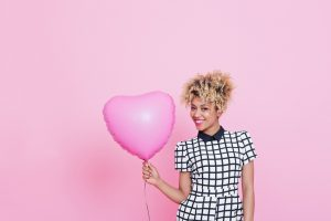 Portrait of beautiful afro american young woman wearing grid check playsuit, standing against pink background and holding Pink Heart Balloon.